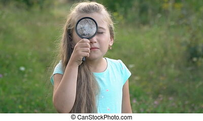 little girl looks through a magnifying glass