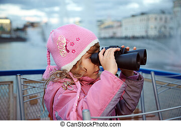 Little girl looks through binoculars, standing on the background of fountains.