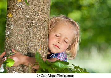 Little girl loves her tree and is hugging the trunk