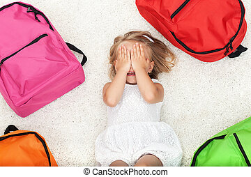Little girl lying among colorful school bags
