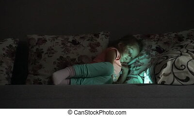 Little girl lying down at sofa and watching cartoons in the evening at tablet