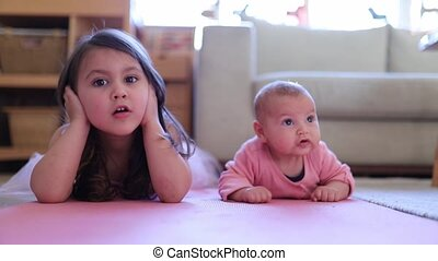 FHD Video of a little girl and a baby lying face down on a pink rug with a bright natural light behind them