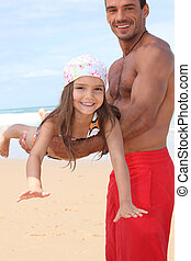 little girl lying down on father's arms on the beach