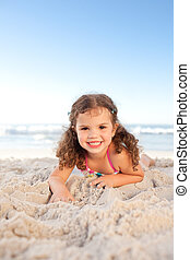 Little girl lying down on the beach