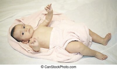 Little girl lying in a towel on a white blanket after bathing