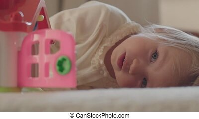 Little girl lying in bed and looking at camera.