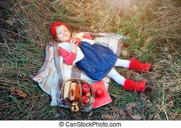 Little girl lying in grass on a plaid with a basket of fruit.