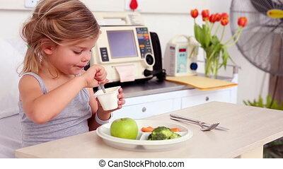 Little girl lying in hospital bed eating lunch - Little girl...