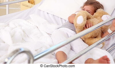 Little girl lying in hospital bed in the hospital ward