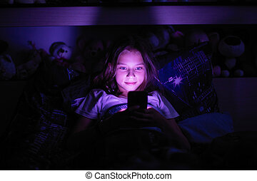 Little girl lying in the dark under a blanket looking at smartphone.