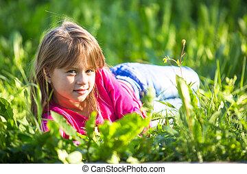 Little girl lying in the grass.