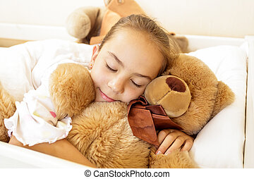 girl lying on bed with big brown teddy bear