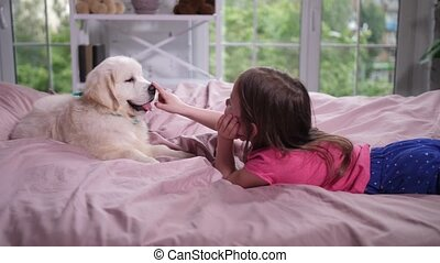 Little girl lying on cozy bed with puppy - Side view of...