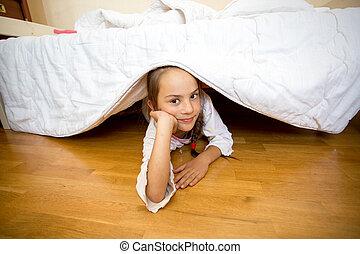 little girl lying on floor under bed - Portrait of little...