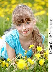 Little girl lying on grass in flower.
