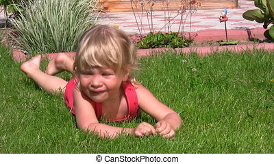 little girl lying on grass in outlet and dangles legs -...