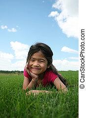 Little girl lying on grass in summer