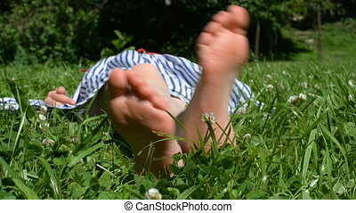 Little girl lying on green grass