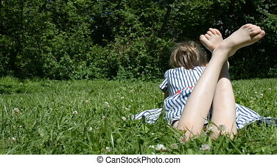 Little girl lying on green grass.