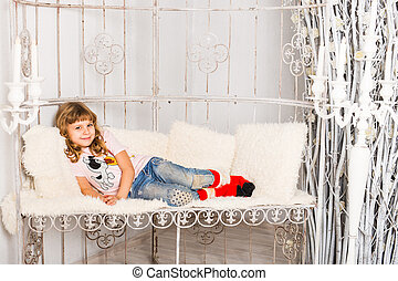 Little girl lying on sofa at home. Kid playing having fun on couch.