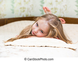 Little girl lying on the bed