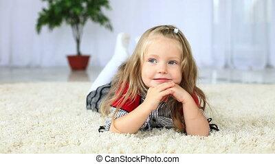 Little girl lying on the carpet