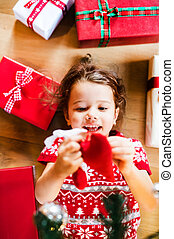Little girl lying on the floor among presents.