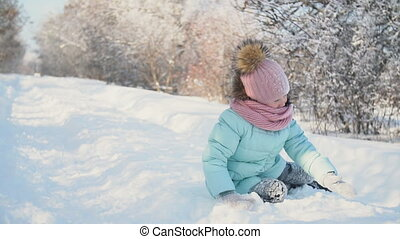 little girl lying on the snow
