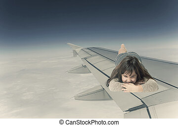 Little girl lying on the wing of an aircraft facing the camera