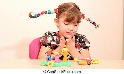 little girl make family figure