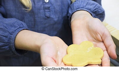 little girl makes a cookie in the kitchen