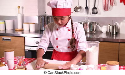 Little girl makes dough in kitchen with rolling pin - Lovely...