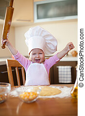 Little girl makes dough on kitchen with rolling pin