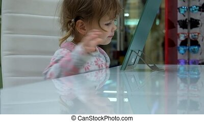 Little girl makes faces in front of a mirror