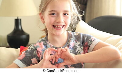 Little girl making a heart symbol - Cute young schoolgirl...