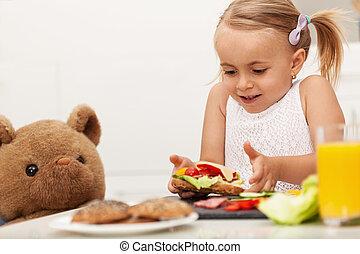 Little girl making a sandwich to her teddy bear