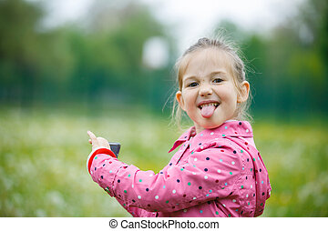 Little girl making faces and showing her tongue to her father that disturbed her at taking a picture with smart phone. Disobedience, cheerful behavior and carefree childhood concept.
