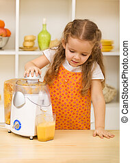Little girl making fresh fruit juice with a kitchen ...