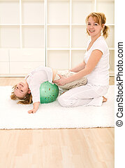 Little girl making gymnastic exercises with her mother