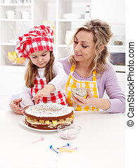 Little girl making her first fruit cake with some help