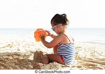 Little Girl Making Sand Castle On Beach