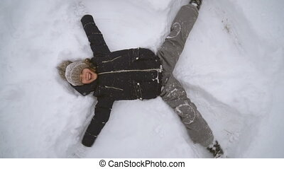 Little girl making snow angel in winter time.