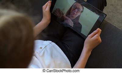 Little girl making video call with school teacher. Distance learning.