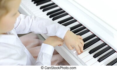 Little girl masterfully plays music on a piano