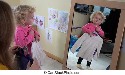 Little girl measure clothes in front of mirror