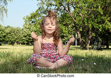 little girl meditates in nature