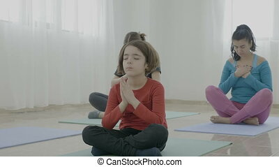 Little girl meditating among middle aged women during a yoga class in a fitness studio