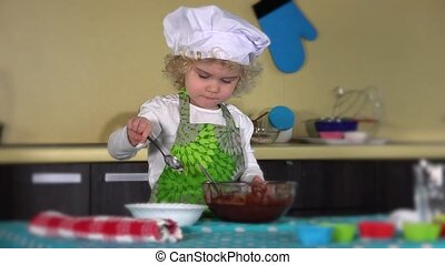 little girl mixes chocolate dough with green apron and chef hat in kitchen. 4K