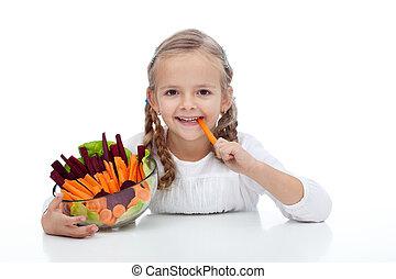 Little girl munching on a carrot stick