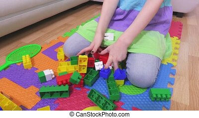 Little girl near colorful toy bricks